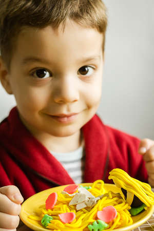 clay modeling: Portrait of cute child posing with his original spaghetti dish, made in colorful plasticine