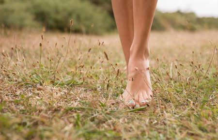 jolie pieds: Belles jeunes jambes des femmes marchant sur l'herbe en été Banque d'images