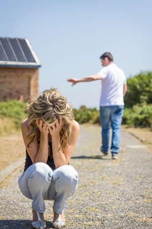 Unglückliche Frau im Fokus weinend und wütend Mann verlassen auf dem Hintergrund nach Streit