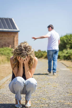 Unhappy woman in focus crying and angry man leaving on the background after quarrel Stock Photo
