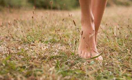 piedi nudi di bambine: Belle giovani donne gambe camminando sull'erba in estate