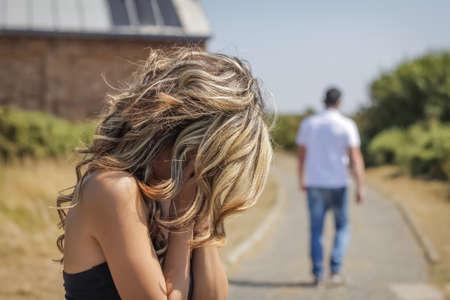 Nešťastná žena v zaměření pláče a rozzlobený muž odchází na pozadí po hádce
