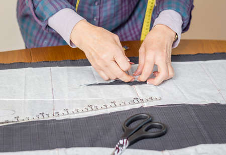tailor suit: Woman dressmaker design tailor pattern for a suit on the table Stock Photo