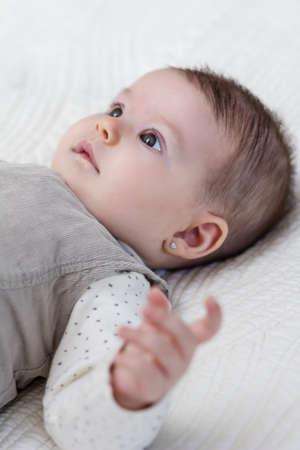 babies hands: Happy cute baby girl lying on back Stock Photo
