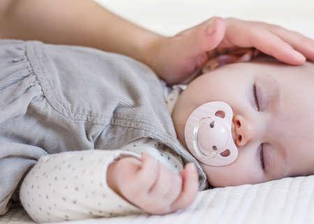 Bàn tay của mẹ vuốt ve bé gái dễ thương của mình với núm vú ngủ lại trải giường màu trắng