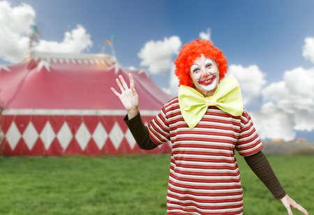 Niña de payaso divertido con el lazo gran arco y maquillaje sobre fondo de circo carpa