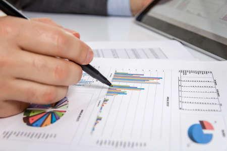 revisando documentos: El hombre de negocios revisar documentos gráficos con el ordenador tableta digital en el lugar de trabajo