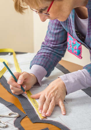 Woman dressmaker drawing tailor pattern with pencil for a suit on the table photo