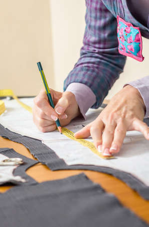 tailor suit: Woman dressmaker drawing tailor pattern with pencil for a suit on the table