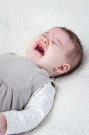 bedcover: Cute baby girl crying over white bedcover