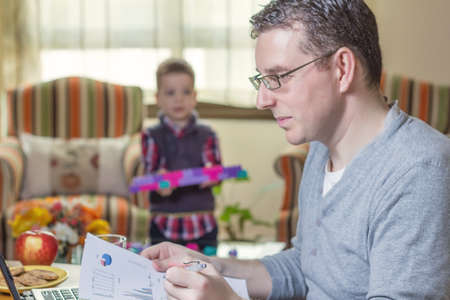 Father working hard in home office with notebook and his boring son playing  photo