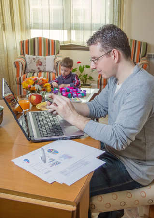 Father working hard in home office with smartphone and his boring son playing  photo