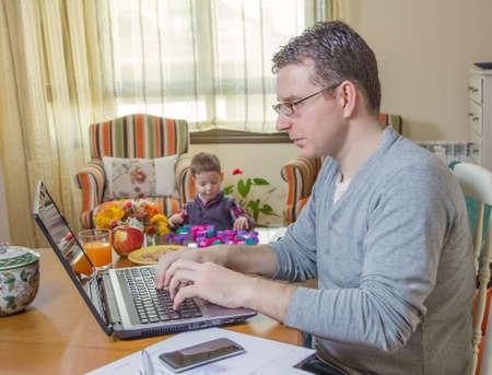 trabajando duro: Padre de trabajo duro en la oficina en casa con el port�til y su hijo aburrido jugando Foto de archivo
