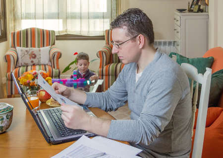 Father reading business documents in home office and his boring son playing  photo