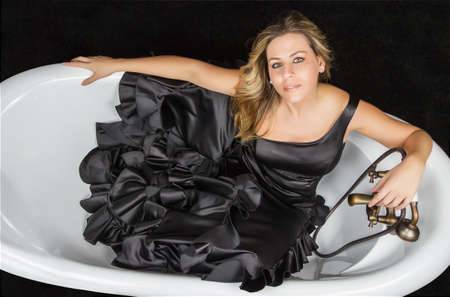 Portrait of beautiful fashion girl with black spanish flamenco dress posing in a vintage bathtub photo