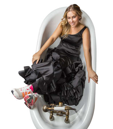 Portrait of beautiful fashion girl with black spanish flamenco dress and running shoes posing in a vintage bathtub on white background photo
