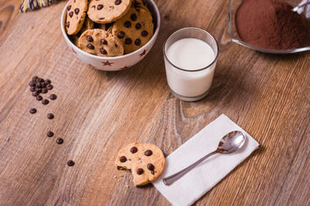 Closeup of chocolate chip cookies on stars bowl and milk glass over a wooden background photo