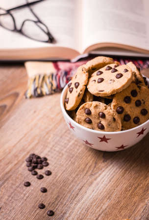 Closeup of chocolate chip cookies on stars bowl and book over a wooden background photo