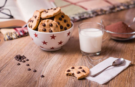 Closeup of chocolate chip cookies on stars bowl and milk glass over a wooden background  Image focused in cookie bite photo