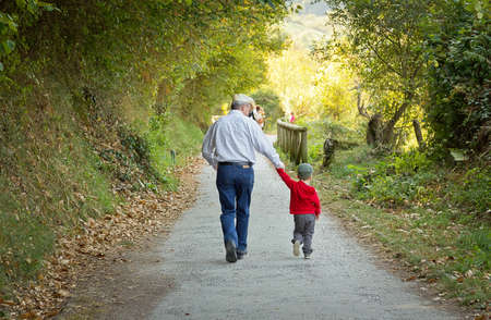 Back view of grandfather and grandchild walking in a nature path