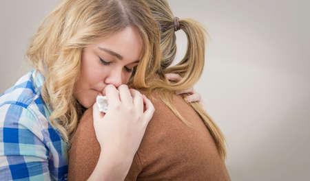 Close-up op trieste tiener dochter huilend door problemen in de schouder van haar moeder Moeder omarmen en troostende dochter Stockfoto