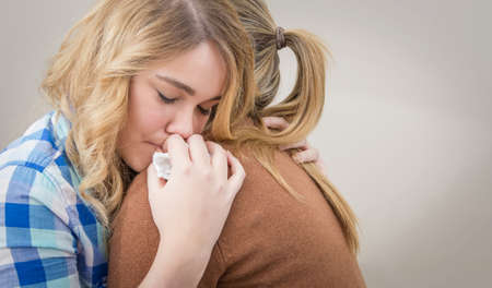 Closeup on sad teen daughter crying by problems in the shoulder of her mother  Mother embracing and consoling daughter  Stock Photo