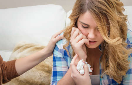Hands of mother closeup consoling sad teen daughter crying by problems