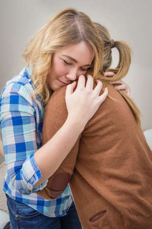 soothe: Closeup on sad teen daughter crying by problems in the shoulder of her mother  Mother embracing and consoling daughter  Stock Photo