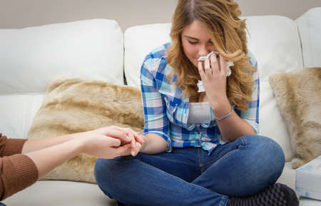 sad teen: Hands of mother closeup consoling sad teen daughter crying by problems