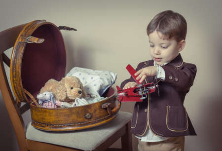 Vintage portrait of cute little boy playing with antique tin toys found in a old case  Retro style concept  photo