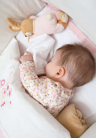 Portrait of cute baby girl sleeping in a cot with pacifier and stuffed toy