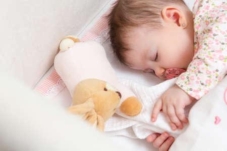 Porträt von niedlichen Baby-Mädchen schlafen im Kinderbett mit Schnuller und Spielzeug gefüllt