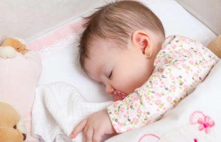 Chân dung dễ thương bé gái ngủ trong giường cũi với núm vú giả và đồ chơi nhồi bông