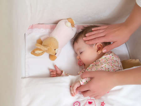 Hands of mother caressing her cute baby girl sleeping in a cot with pacifier and stuffed toy photo