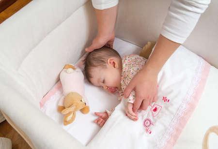 Handen van moeder streelt haar schattige baby meisje slapen in een wieg met fopspeen en knuffel