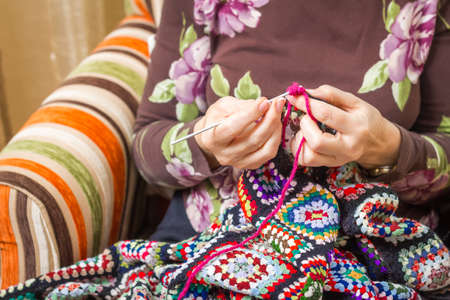 bedcover: Hands of senior woman knitting a vintage wool quilt with colorful patches Stock Photo