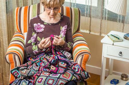 trabajo manual: Retrato de la mujer mayor de tejer una colcha de lana clásicos con parches de colores