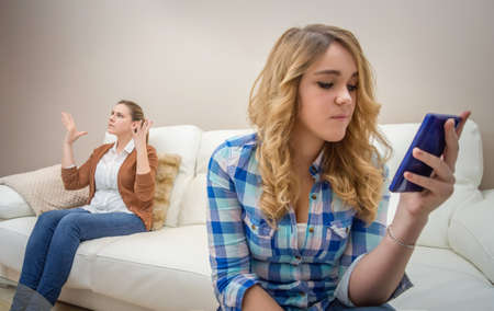 Teenage daughter looking messages in a smartphone and ignoring her furious mother photo