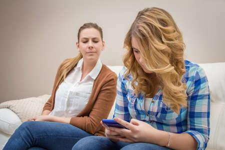 Podezřelá matka špionáž její dospívající dcera při pohledu zpráv ve smartphonu Reklamní fotografie