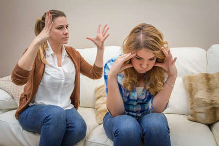 Furious young mother in a discussion with her teenage daughter  Problems between generations concept