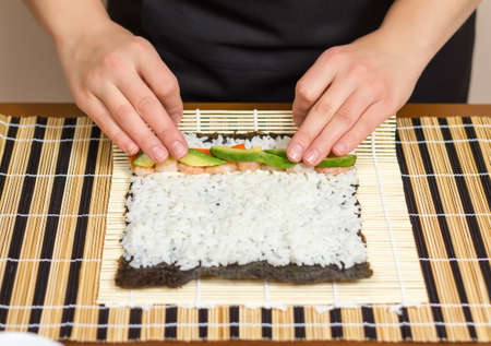 rolling: Hands of woman chef rolling up a japanese sushi with rice, avocado and shrimps on nori seaweed sheet