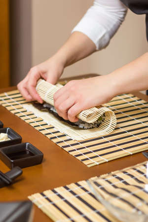 Hands of woman chef rolling up a japanese sushi with rice, avocado and shrimps on nori seaweed sheet photo