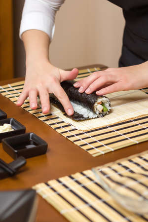 moisten: Woman hand moistening with water a edge of japanese sushi to close the roll