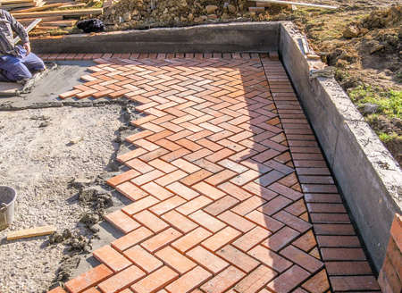 Orange brick paving stones pattern in the construction process of a courtyard