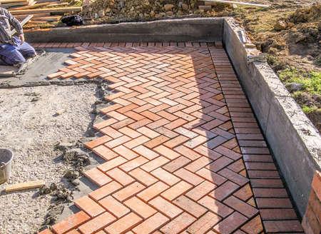 Oranje bakstenen straatstenen patroon in het bouwproces van een binnenplaats