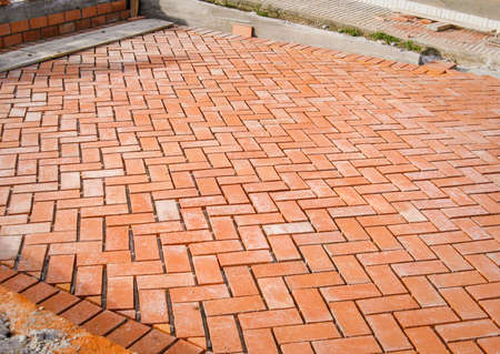 brick mason: Orange brick paving stones pattern in the construction process of a courtyard