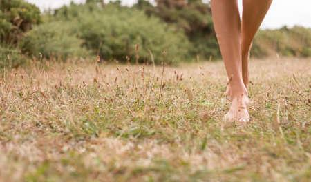 Schöne junge weibliche Beine zu Fuß auf dem Gras im Sommer