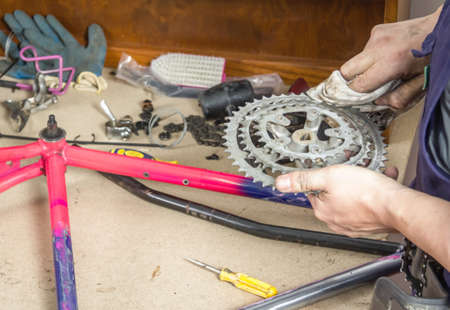 Hands of real bicycle mechanic cleaning chainring bike over workshop table in the repair process photo