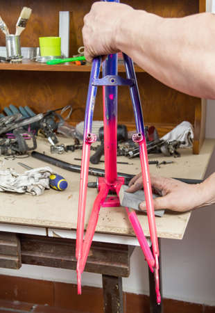 bicycle frame: Hands of real bicycle mechanic sanding damaged frame bike in a workshop