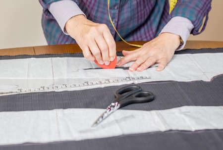 Woman dressmaker design tailor pattern for a suit on the table photo